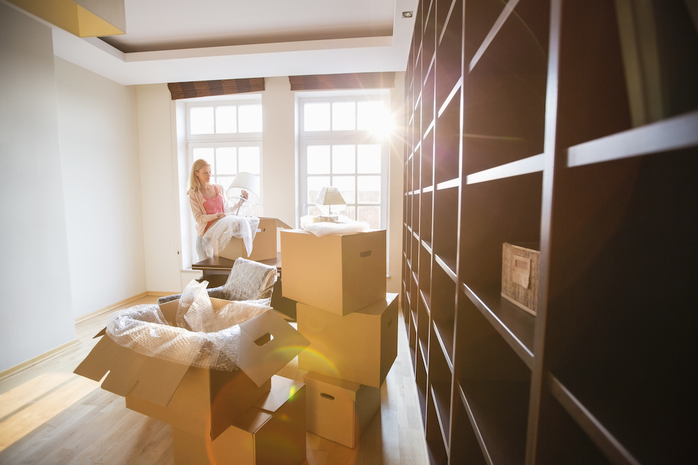 woman unpacking moving boxes in apartment